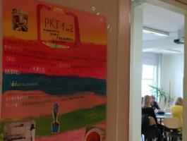 Grupp inimesi vestlemas, Esiplaanil õppijate poolt valmistatud plakat oma eriala kohta.