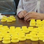 Kaitstud töö teenuse lihttöö töötoas majoneesikorkidele hõbepaberi panemine